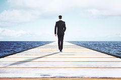 Businessman walking on a straight road to the horizon. Close up Royalty Free Stock Photos