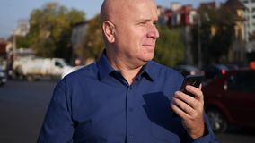 Businessman walking on the street in downtown text using cellphone connection.  stock footage