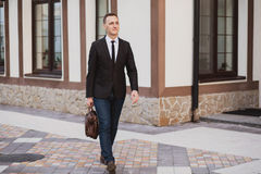 Businessman walking on the street. Holding a briefcase in his hands Stock Photography