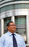 Businessman walking on street of KLCC twin tower. Royalty Free Stock Images