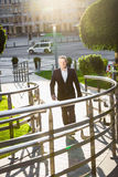 Businessman walking on street at sunny day Stock Photo
