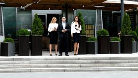Businessman walking on the street with their secretaries. In front of office stock footage