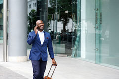 Businessman walking with a suitcase and talking on phone. Portrait of an african businessman walking with suitcase and talking on mobile phone Royalty Free Stock Image