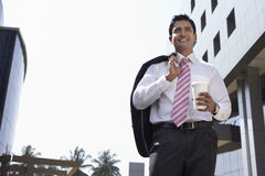 Businessman Walking With Takeaway Coffee Cup Outdoors. Low angle view of happy young businessman walking with takeaway coffee cup outdoors Royalty Free Stock Photos