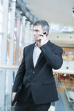 Businessman walking and talking on mobile phone Stock Photography