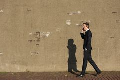 Businessman walking and talking on mobile phone Royalty Free Stock Images