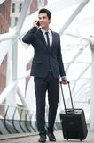 Businessman walking and talking on the phone at metro station. Portrait of a young businessman walking and talking on the phone at metro station Stock Photo