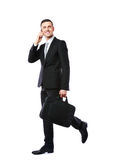 Businessman walking and talking on the phone Stock Image