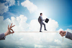 The businessman walking on tight rope in business concept. Businessman walking on tight rope in business concept Stock Image