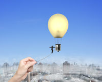 Businessman walking tightrope woman hand pulling lightbulb hot a. Businessman walking tightrope woman hand pulling, toward yellow lightbulb shape hot air balloon Stock Photography