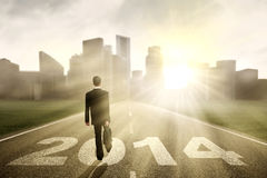 Businessman walking to the New Year 2014. With cityscape background Royalty Free Stock Images