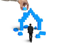 Businessman walking toward house shape of stack blocks Royalty Free Stock Images