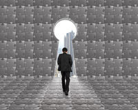 Businessman walking toward key shape door with puzzles backgroun Royalty Free Stock Photography