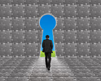 Businessman walking toward key shape door on puzzles wall Royalty Free Stock Photography