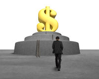 Businessman walking toward large money symbol Royalty Free Stock Photo