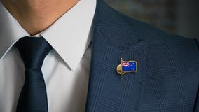 Businessman Walking Towards Camera With Country Flag Pin-New Zealand. In focus stock footage