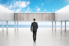 Businessman walking towards concrete exterior Royalty Free Stock Image