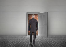 Businessman walking towards door open but blocked by red brick w royalty free stock photos