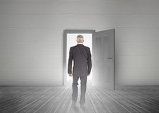 Businessman walking towards door showing light. In a dull grey room Stock Photography
