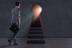 The businessman walking towards light from keyhole. Businessman walking towards light from keyhole Stock Photos