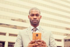 Businessman walking in town with mobile phone Stock Image