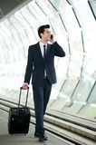 Businessman walking on train station platform and talking on phone Stock Photo