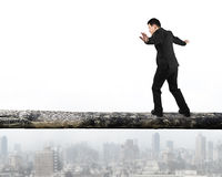 Businessman walking on the tree trunk Stock Image
