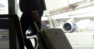 Businessman walking with trolley bag. At the airport stock video footage