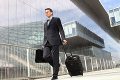 Businessman walking with trolley and bag Stock Photography