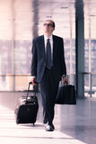 Businessman walking with trolley and briefcase. Portrait of adult businessman walking with trolley and briefcase Stock Images
