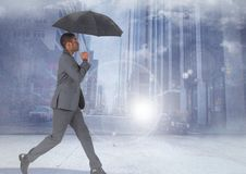 Businessman walking with umbrella in city. Digital composite of Businessman walking with umbrella in city Royalty Free Stock Photography