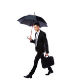 Businessman walking with umbrella Stock Image