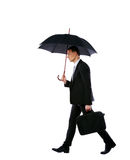 Businessman walking with umbrella Stock Photos