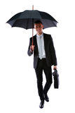 Businessman walking with umbrella Royalty Free Stock Image