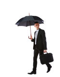 Businessman walking with umbrella Stock Images