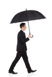 Businessman walking with an umbrella Royalty Free Stock Images