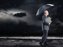 Businessman Walking Under Umbrella In Rain Stock Photos