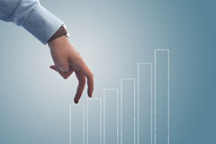 Businessman walking up the bar chart. With his fingers Royalty Free Stock Image