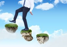 Businessman walking up steps of floating rock platforms in sky Royalty Free Stock Image
