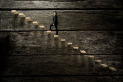 Businessman walking up on wooden stairway Royalty Free Stock Photography