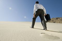 Businessman Walking Uphill In Desert Stock Photo