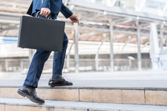 Businessman walking upward on the stair. Close up shot of businessman holding leather briefcase while walking upward on the stair outdoor in city Stock Photo