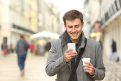 Businessman walking and using a smart phone Stock Photos