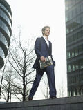 Businessman Walking On Wall Outside Office Building Stock Photography