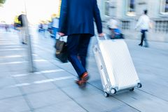 Businessman Walking With A Trolley Case In The City Stock Photos