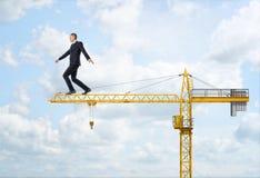Businessman walking on yellow construction crane Royalty Free Stock Photos