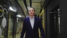 Businessman walks along room with glass wall to hallway