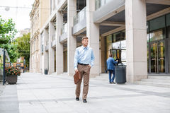 Businessman walks with briefcase Stock Images