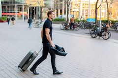 Businessman walks with casual clothing in the city. Businessman walks with casual clothing and a trolley bag in the city Stock Images