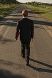 Businessman walks with red file Royalty Free Stock Images